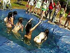 Girls wrestle in a homemade pool outside